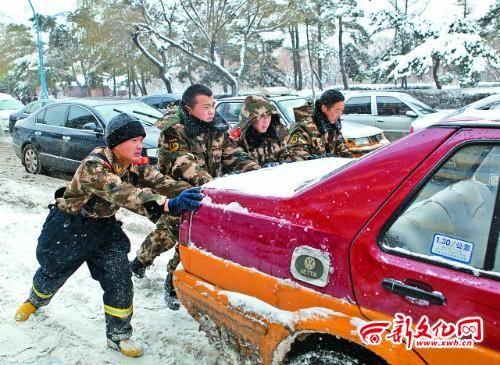 长春市东民主大街上,消防官兵帮助打滑的车辆驶出积雪路段 实习记者 蒋盛松 摄