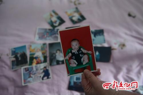 """东女士常常拿出""""儿子""""小时候的照片翻看 记者 刘阳 摄"""