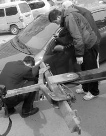 工作人员正在试图将轿车抬离 新文化报 记者 李洋 摄