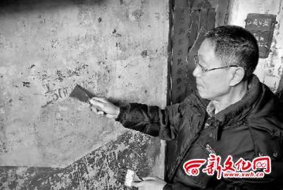 张仁正在清理楼道非法广告 记者 李洪洲 摄