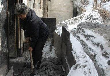 魏桂云在清理家门口的积冰 记者 迟久阳 摄