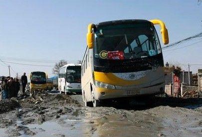 校车被困在马路大坑中 记者 黄云龙 摄