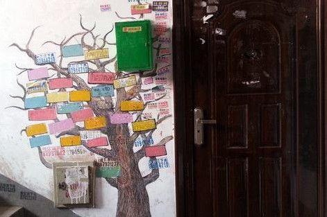 为了楼道美观,小伙在非法广告上画了棵大树 记者 吴廷 摄
