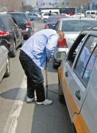 昨天9时45分,在长春市人民大街与自由大路交会处,趁堵车,淡定的的哥赵师傅拿出打气筒给车胎补气 本报记者黄云龙摄