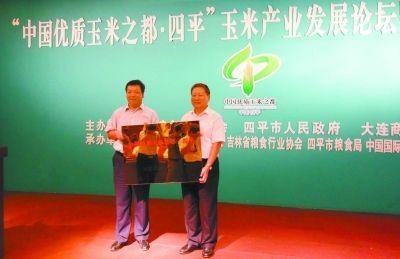 中国粮食行业协会会长聂振邦(右)向四平市市长石国祥