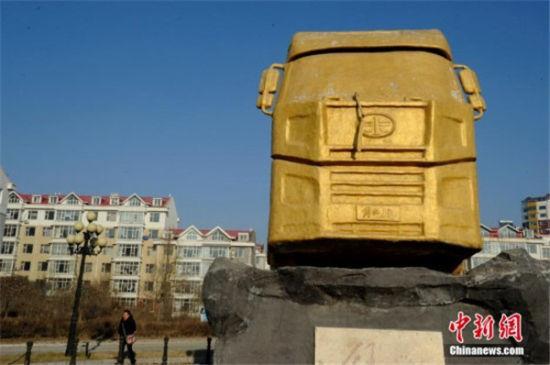 """全身涂满金黄色油漆的""""土豪金""""汽车雕塑矗立在长春市一小区内,吸引市民围观"""